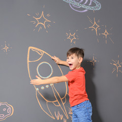 Cute little child playing with chalk rocket drawing on grey background