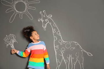 African-American child playing with chalk drawing of giraffe and flowers on grey background