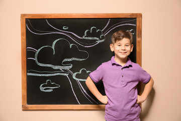 Cute little child standing at blackboard with chalk drawn sky and clouds
