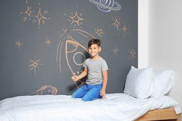 Little child drawing rocket with chalk on wall in bedroom