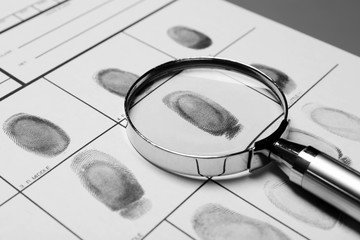 Magnifying glass and criminal fingerprint card, closeup
