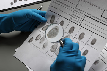 Criminalist exploring fingerprints with magnifying glass at table, closeup