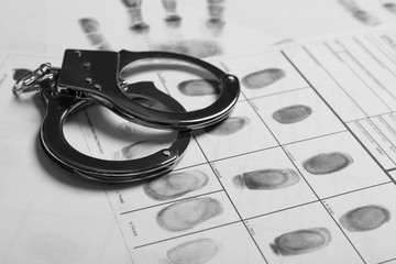Police handcuffs and criminal fingerprints card, closeup