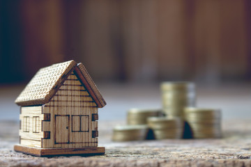 real esatae investment,image of house model with stack of coins.