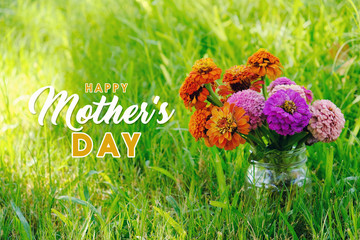 Mother's Day zinnia flowers in vase sitting in grass outside.  Cheery and bright holiday image with text for mom.