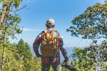 male traveler photographer fascinated by illuminated nature mountains at morning time.