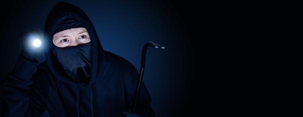 Maskierter Einbrecher in der Nacht mit Brecheisen und blau schwarzen Hintergrund - fototapety na wymiar