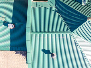 aerial top view of green corrugated metal house roof with installed pipes of ventilation system