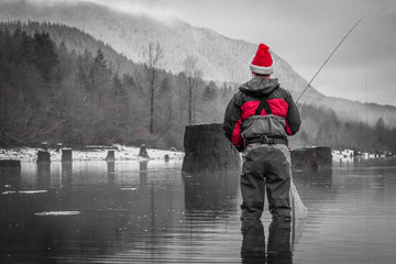 Black, White & Red Photo of a Man Fly Fishing in a Christmas Santa Hat - Wearing a Red Jacket and Waders, with Trees and Mountains in the Background in the Pacific Northwest on a Cloudy Winter Day