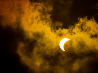 Moody, Vibrant Orange Nature Photo of a Partial Crescent Shaped Solar Eclipse in the Daytime from 2017, Close Zoom with a Cloudy Sky and Dark Shadows