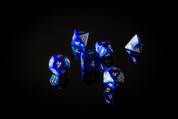 Moody, Shadowy Photo of Six Blue Role Playing Gaming Dice Displayed on a Reflective Surface, with a Dark Black Background