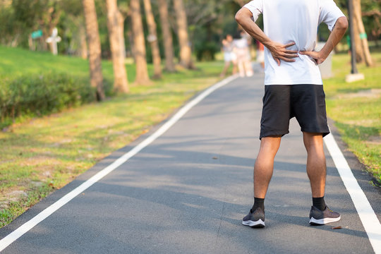 Young fitness man holding his sports leg injury. muscle painful during training. Asian runner having back ache and problem after running and exercise outside morning. sport and healthy concepts