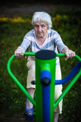 Elderly woman exercise on the street sport playground.