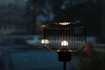 A fragment of a floor-lamp illuminating dim atmosphere of a cafe, light reflected from the wet window with running raindrops.