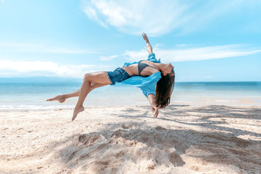 Photograph with the effect of levitation, a young beautiful slim woman hanging in the air against the backdrop of the tropical sea and the beach
