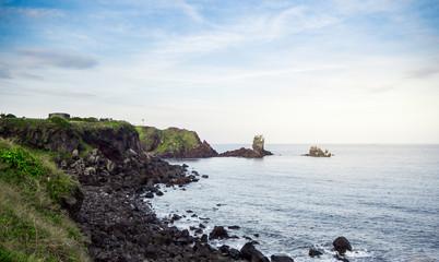 Beautiful blue sea with black sand beach and sky of Jeju island in Korean
