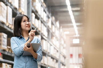 Candid of young attractive asian woman, auditor or trainee staff working in warehouse store counting or stocktaking inventory by smart tablet. Asian entrepreneur, small business or SME concept.