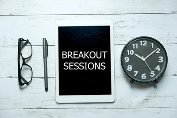 Business concept. Top view of glasses,pen,clock and tablet written with Breakout Sessions on white wooden background.