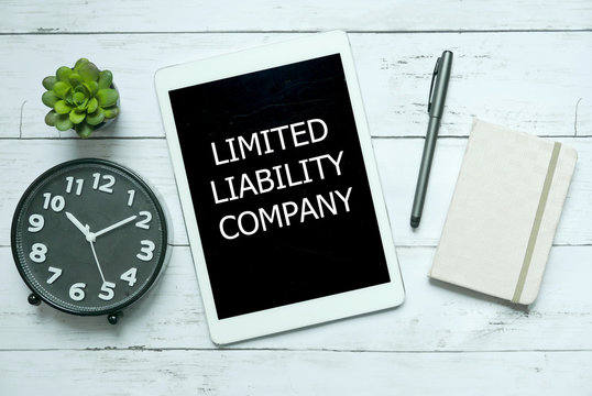Business concept. Top view of plant,clock,pen,notebook and tablet written with Limited Liability Company on white wooden background.