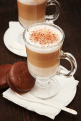 Cappuccino with cinnamon. Cup of coffee on wooden background