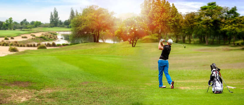 Panorama of Golfer hit sweeping golf ball on blurred  beautiful golf course with sunshine on background.