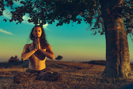 Yogi man meditating at sunset on the hills. Lifestyle relaxation emotional concept spirituality harmony with nature