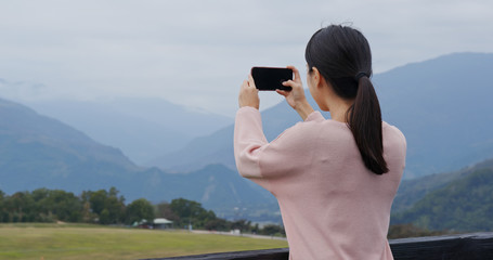 Woman take photo on cellphone in the luye highland at Taitung