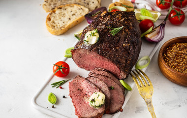 Roast beef with sauce and meat fork on white background. Copy space.
