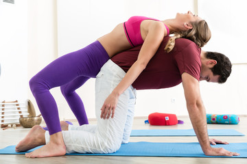 Man and woman practicing pair yoga in morning