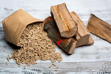 Scheitholz und Holzpellets liegen nebeneinander auf Holztisch,direkter Vergleich von Brennstoffen
