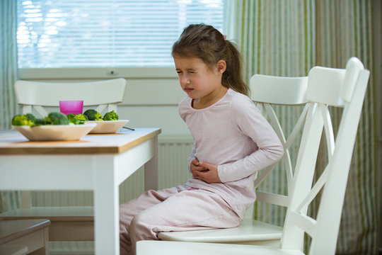 Child sitting at the table in the kitchen with stomach pain. Hands on belly. Little girl suffering