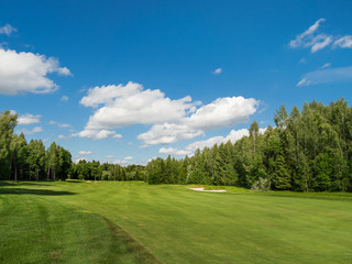 Countryside golf course. Green cutted grass on field, forest and blue sky. Cloudscape in sunny day. Russia.