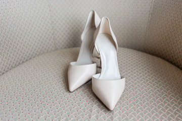 Pair of white shoes commonly called D'Orsay on beige chair.
