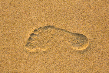 right foot print in yellow sand close up
