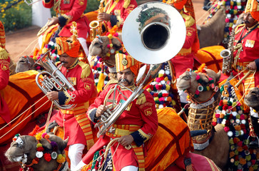 Indian Border Security Force (BSF) soldiers play musical instruments as they ride their camels during the full dress rehearsal for the Republic Day parade in New Delhi