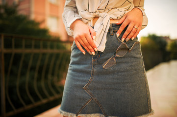 Close up photo of eyeglasses on woman, wear on jeans skirt.