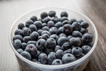 Ripe tasty blueberries and berries on a wooden table in a bowl