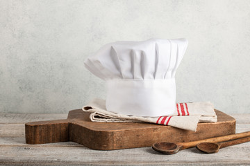Chef's hat, antique cutting board and wooden spoons