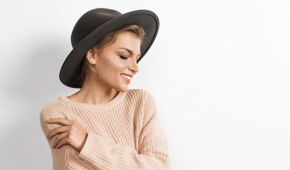 Wall Mural - Portrait of charming gentle girl in cozy beige knitted sweater and trendy hat posing and looking down. Modern fashion and autumn concept. Copy space in right side