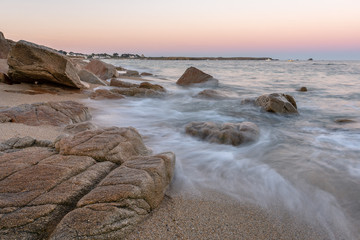 French landscape - Bretagne. A beautiful beach with rocks and port in the background at sunrise.