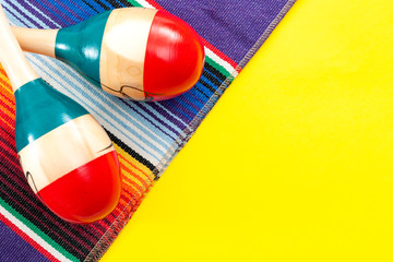 Mexican fiesta and Cinco de Mayo party concept theme with minimalist image of red and blue maracas and traditional colorful rug called a serape on yellow background with copy space for text