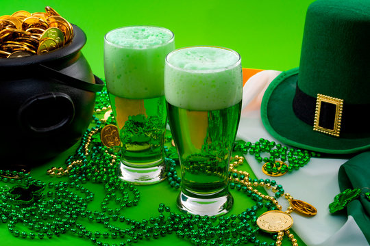 The luck of the Irish meme and Happy St Patricks day concept theme with two glasses of dyed beer, leprechaun hat, beads necklace and pot of gold coins on the Ireland flag isolated on green background