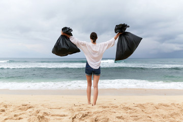 Cheerful volunteer woman with hands up holding two big black bags full of trash, the action of collecting trash from the beach