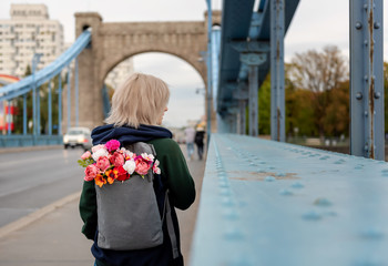 Photo from the back of young blonde woman with bouquet of flowers in backpack is standing on the Grunwald bridge, Wroclaw, Poland.