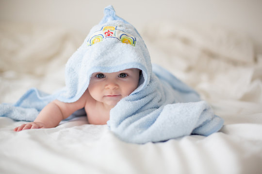 Cute little baby boy, relaxing in bed after bath, smiling happily