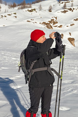 A hiker with snowshoes takes some photos at the sunny snowy landscape of the Alpe Sangiatto above Alpe Devero in Piedmont, Italy.