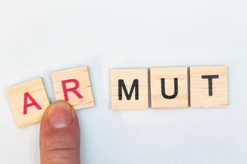 Das Wort Mut wird durch die Buchstaben Aund R erweitert, dies ergibt das Wort Armut