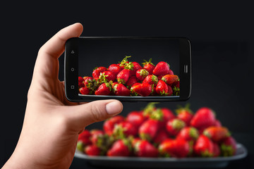Hands with the phone takes pictures of strawberries. Ripe fresh strawberries in a white plate on a black background. Photos of the smartphone for the post in social networks.