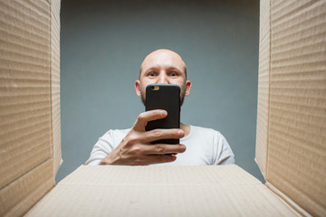 A man takes a picture of the contents of the box on the phone. The concept of receiving the order, cargo, goods. Damaged order.