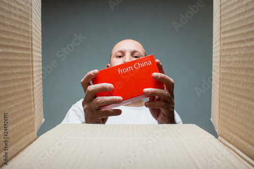 3b510e206fdac A man takes a small box with the text From China from an open ...
